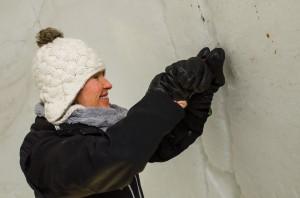Det är mycket jobb med att få igloon riktigt vit på insidan eftersom snön inte är helt ren. Det är en hel del sten och smuts som syns på väggarna. Här är det  Brooke Erdman som rensar bort smutsen. De hål som blir fylls sen med ren snö.
