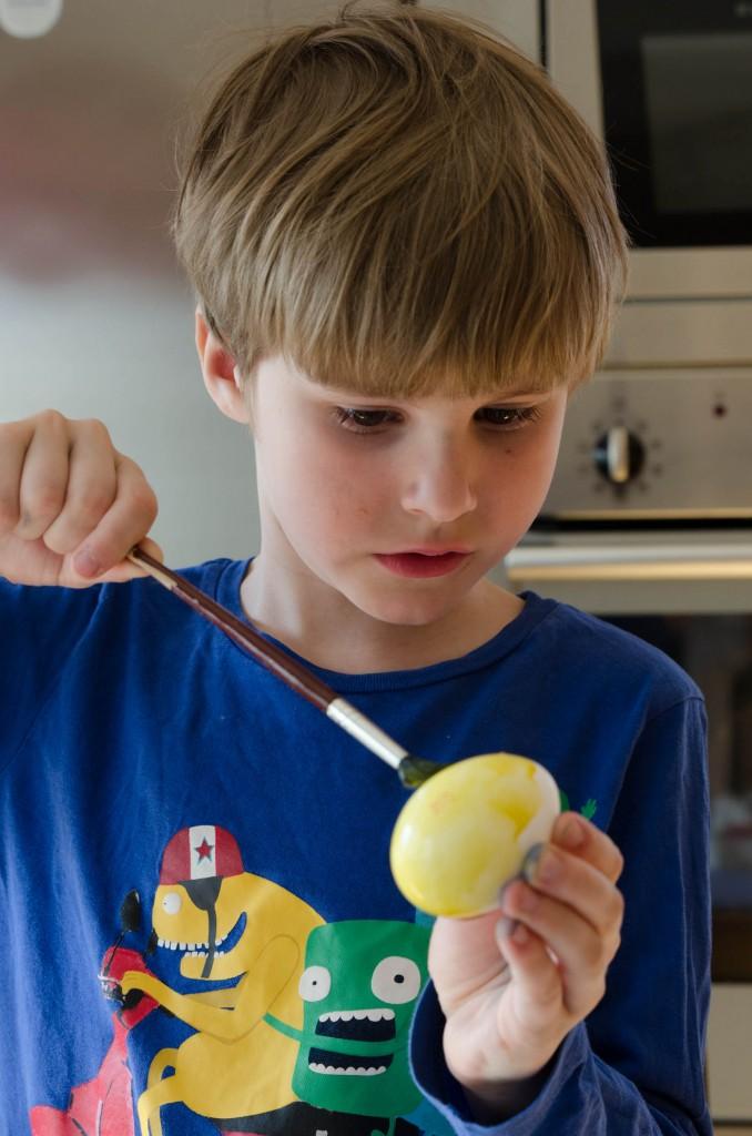 Simon målar påskägg.