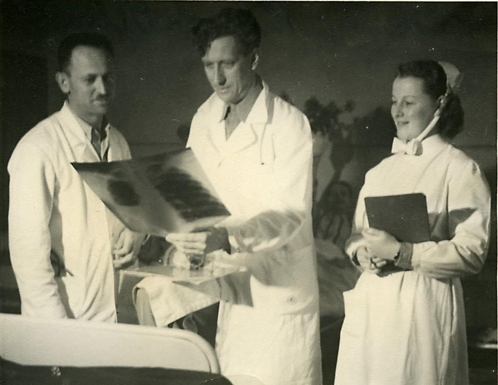 Ett par läkare och en sjuksyster studerar en röntgenplåt. På baksidan står det Dano, Müller och Sylva.