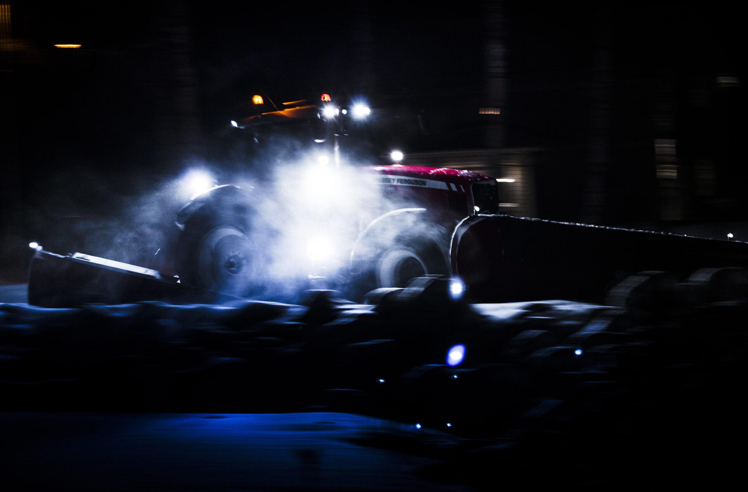 Traktor i snörök och mörker.